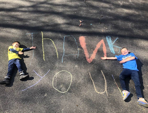 kids saying thank you with chalk on ground
